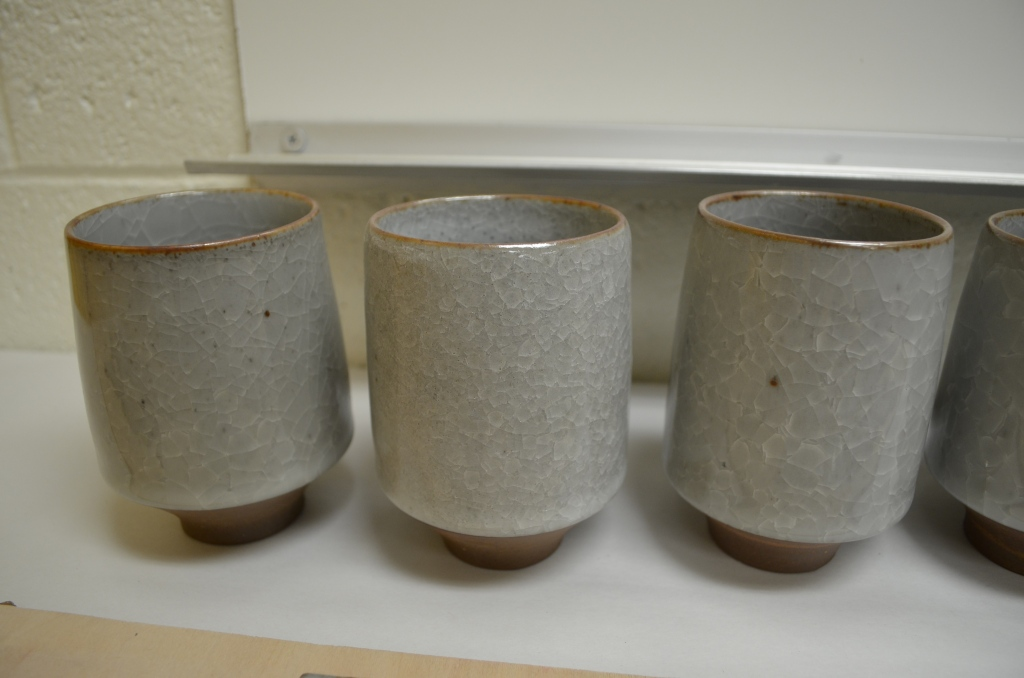 Three cups, same clay, same glaze, completely different firing and cooling regimes.