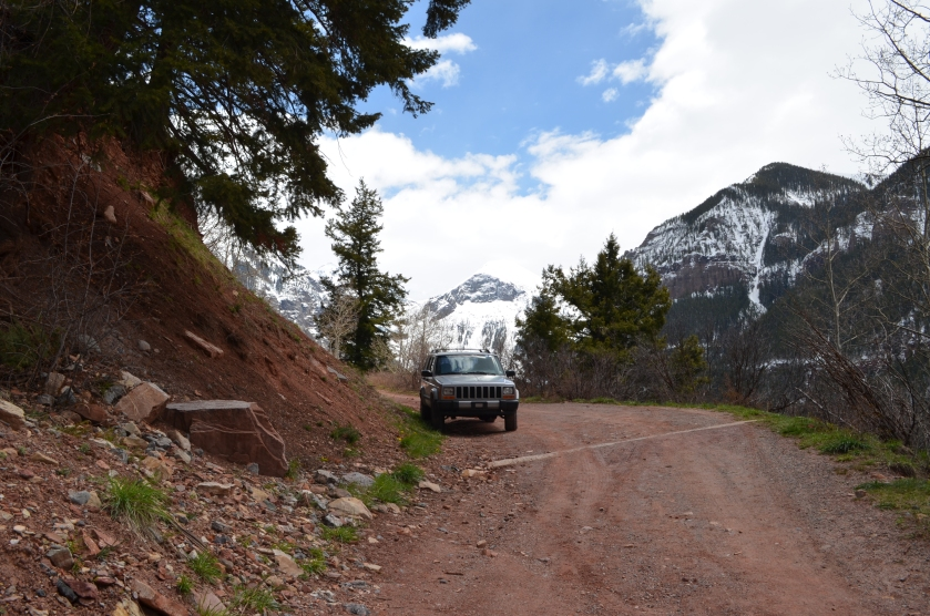 Jeepster parked next to a clay bank with Mount Telluride in the background.